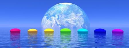Ligne de sept cailloux aux couleurs des chakras sur l'océan d'un bleu profond, en face de l'ombre de la terre, de l'horizon en arrière-plan
