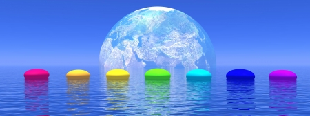 Line of seven pebbles with chakras colors upon the deep blue ocean, in front of earth shadow, horizon in the background Stock Photo
