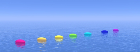 Seven pebbles with chakras colors upon the deep blue ocean, horizon in the background Stock Photo