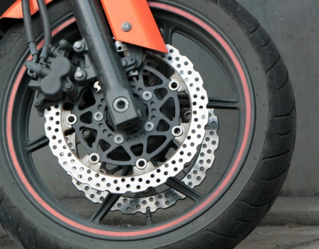 Close up of the front wheel of a red motorbike photo