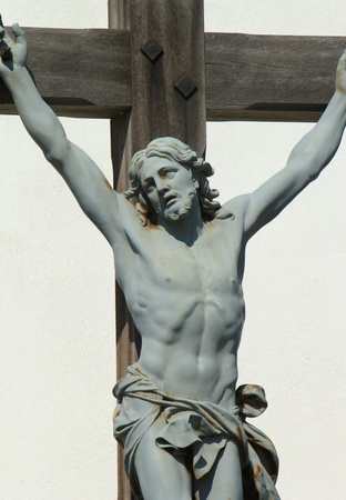 naked statue: Close up of green statue of Jesus-Christ on a wood cross Stock Photo