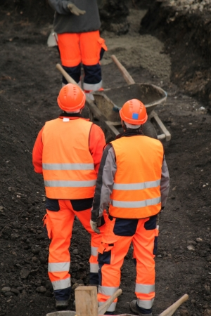 Workers wearing orange uniform talking on the construction site photo
