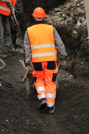 Worker wearing orange uniform pushing wheelbarrow to another worker on the construction site photo