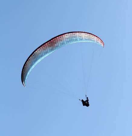 paraglide: Paraglider flying with colordul paraglide in the blue sky Stock Photo
