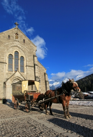 Brown horse and carriage in front of Notre-Dame de lAssomption church by beautiful day, Grand-Bornand, France photo