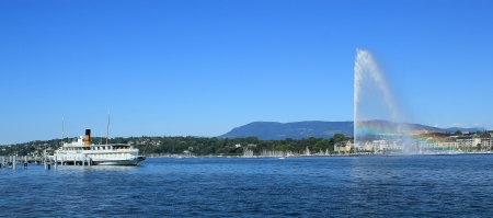 Water fountain with rainbow and old steamboat on the Geneva lake by beautiful summer day, Geneva, Switzerland