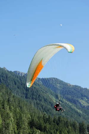 paraglide: Paragliding tandem upon the Alps mountains and fir trees by beautiful day in Chamonix, France