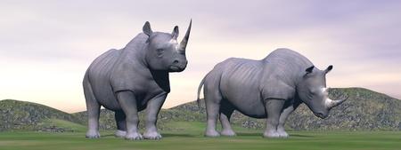 standing alone: Two rhinoceros standing alone in green landscape