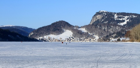 Panoramic view on the frozen lake of the Joux valley and Le Pont village by winter day, Vaud canton, Switzerland photo