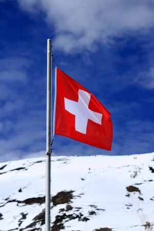 Swiss flag in the Alps mountains by beautiful cloudy day photo