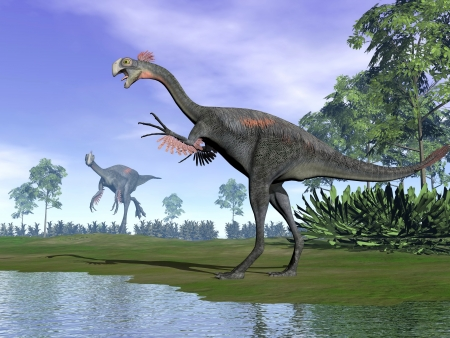 Two gigantoraptor dinosaurs standing in nature with trees next to water  Stock Photo