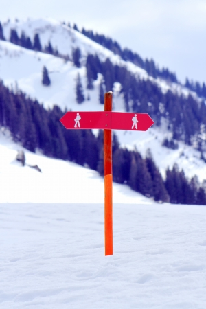 Two red signs for walkers in the snowy mountain photo