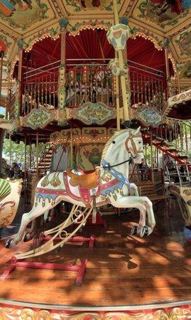 View of the inside of a colorful carousel with beautiful white horses