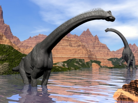 Two brachiosaurus dinosaurs in water next to red rock mountains by beautiful day Stock Photo
