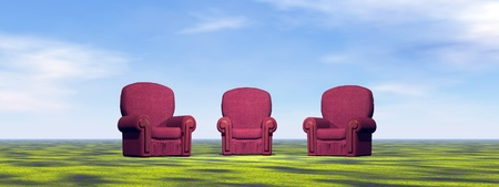 Three red vintage chairs for meeting on a green meadow photo