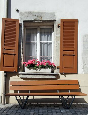 Brown bench under old window with shutters in front of white wall, Estavayer-le-lac, Switzerland Stock Photo - 21220251