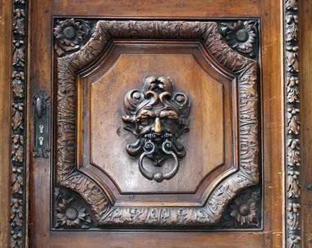 doorknocker: Metallic knocker on an old wooden door in Geneva, Switzerland
