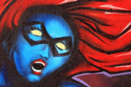 Graffiti on a wall of the blue woman head with red hair photo