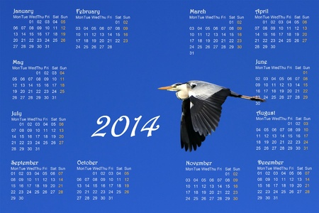 blue heron: 2014 english calendar with great heron flying across a deep blue sky by sunrise Stock Photo