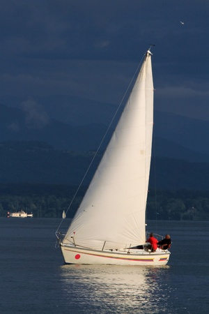 White sailboat sailing on a calm evening with dramatic sunset, Geneva lake, Switzerland photo