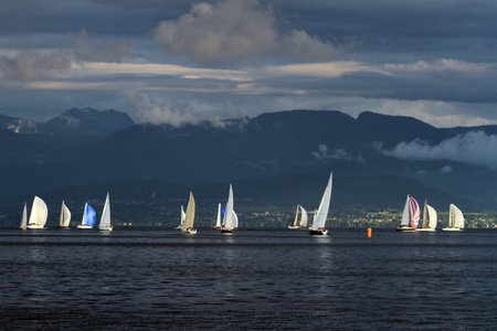 Colorful sailboat sailing on a calm evening with dramatic sunset, Geneva lake, Switzerland photo