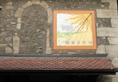 Ancient solar clock on a wall in the old city, Geneva, Switzerland photo