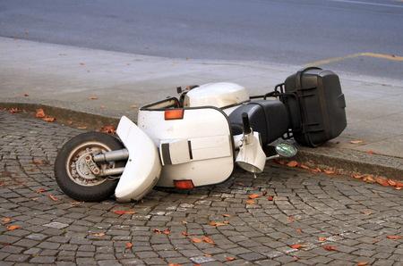 Scooter blanc couché sur la chaussée dans la rue Banque d'images