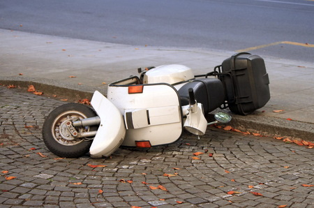 old motorcycle: White scooter lying down on pavement in the street