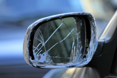 Close up of damaged rearview mirror repaired with scotch on a car