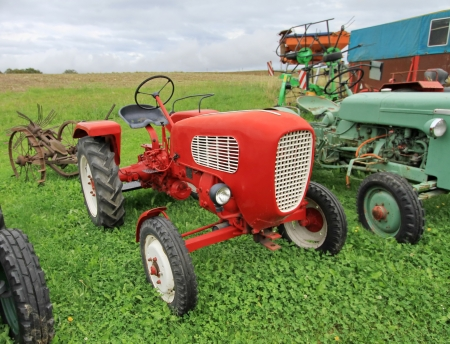 Close up of red antique tractor on green grass by cloudy day photo