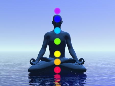 Silhouette d'un homme méditant avec sept chakras coloré sur l'océan par la lumière bleue Banque d'images