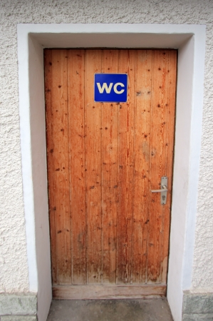 Close up on closed wooden door with WC sign Stock Photo - 24877951