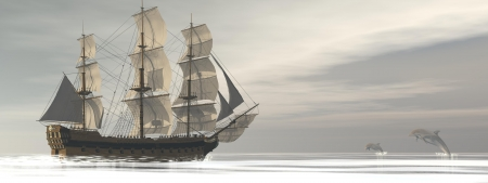 Close up on a beautiful detailed old merchant ship next to two dolphins jumping by grey cloudy day photo