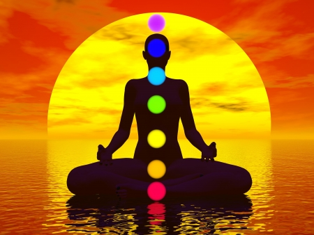 Silhouette of a woman meditating with seven colorful chakras upon ocean by red sunset