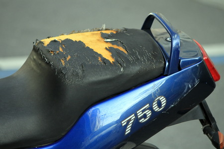 old motorcycle: Close up on a damaged motorbike seat in the street Stock Photo