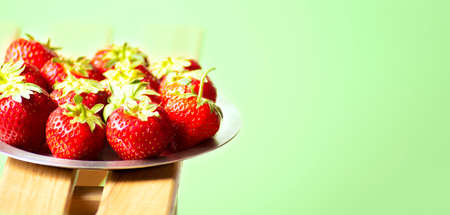 Red strawberries on a metal plate on a light green background, horizontal orientation, closeup side view, banner.