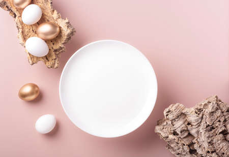 Gold and white Easter eggs lie on the bark of a tree, next to an empty white plate on a powdery background, horizontal orientation, copy space