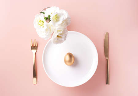 On a white plate lies a golden egg, next to white flowers, and golden cutlery on a powdery background, horizontal orientation, copy space