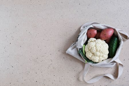 Zero waste food and plastic free shopping concept. Vegetables -  cucumbers, potatoes, cauliflower- in cotton bag.