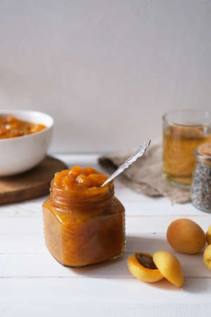 Apricot jam in a glass jar on a white wooden surface. Homemade preservation concept. Selective focus. Reklamní fotografie