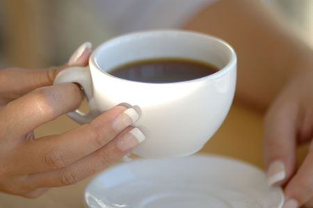 traditonal: A woman holds a traditonal coffee cup filled with black coffee.