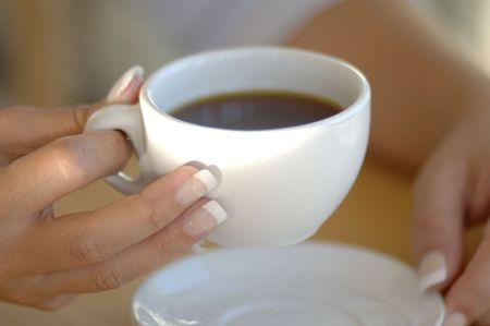 Een vrouw heeft een traditionele kopje koffie gevuld met zwarte koffie.
