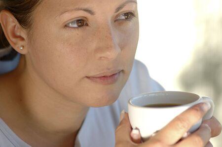 Vrouw met een kopje koffie, het denken.