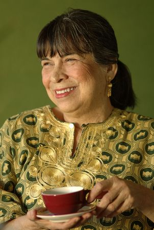 Senior woman of hispanic descent relaxing.  She is wearing an African ethnic blouse holding a cup of coffee.