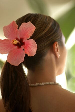 A young woman in a natural tropical environment wearing a large pink Hibiscus flower in her hair and a shell necklace. Stock Photo