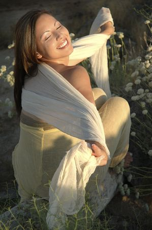 Young woman basking in the sun wearing natural clothing.