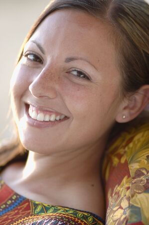 Young woman smiling. Close up portrait while she lounges wearing an ethnic top.