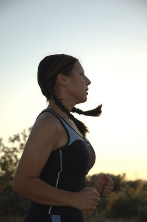 Fit young woman running at dusk.