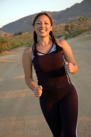 Young woman running outdoors in a natural desert environment.