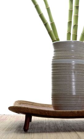 Ornamental bamboo in a neutral tone hand thrown vase sitting on an asian style tray.